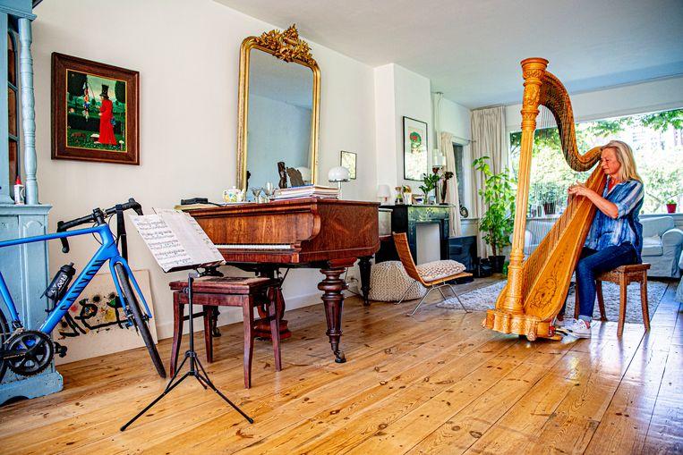 Harpiste Charlotte Sprenkels van het Rotterdams Philharmonisch Orkest musiceert in haar woonkamer. Beeld Getty Images