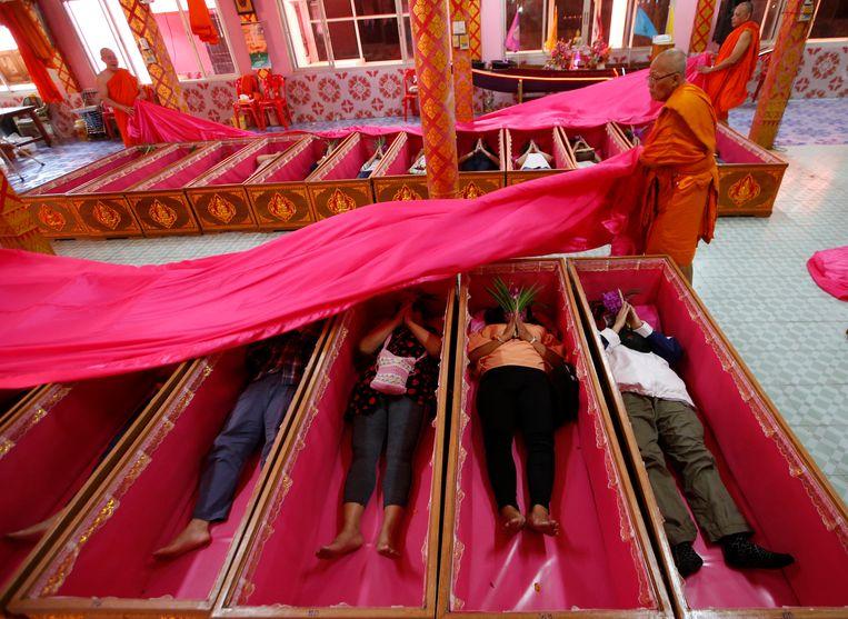 Monniken bedekken op 31 december in doodskisten liggende gelovigen in de Takien-tempel in Bangkok. Zij geloven dat de ceremonie ongeluk afweert en voor een nieuwe start in het nieuwe jaar zorgt. Beeld AP