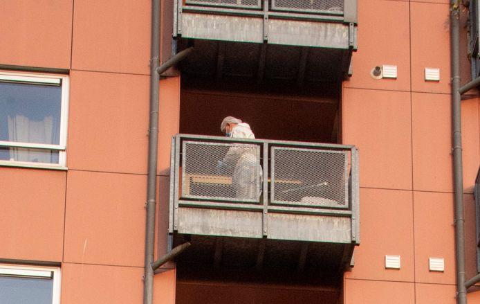 Een medewerker van het parket onderzoekt het balkon van de flat.