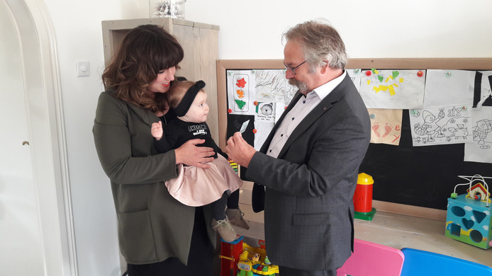 De 8 maanden oude Vaya kijkt met bewondering naar wethouder Cees Lok, die haar persoonlijk haar id-bewijs kwam overhandigen. Vaya is de eerste Roosendaalse die zo'n document thuisbezorgd kreeg.