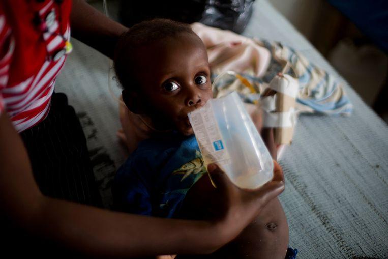 Een slachtoffertje van de orkaan Matthew op Haïti krijgt medicijnen tegen cholera. Van dit soort beelden gaat een sterk emotioneel appel uit, hoewel de impact van liefdadigheid vaak beperkt is. Beeld AP