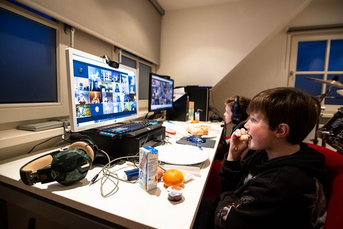 Ties Brouwers (11, voor) en zijn broer Wietse zitten in de gamekamer achter het voorleesontbijt, de avond van tevoren thuis bezorgd door de eigen basisschool De Vonder.