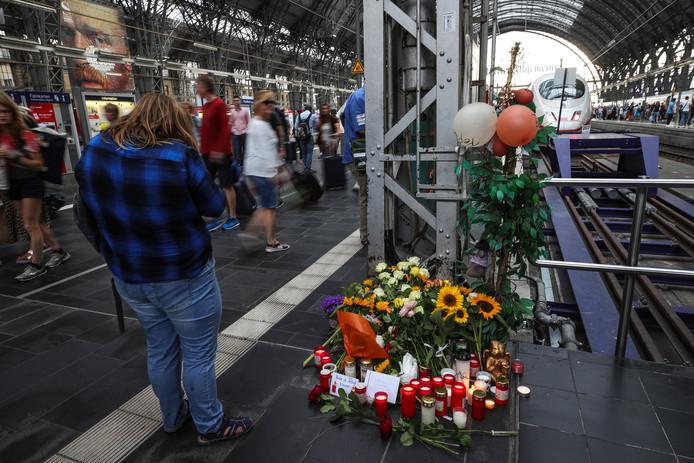 Bloemen, kaarsjes en handgeschreven steunbetuigingen bij de plaats delict op perron 7 in het station van Frankfurt.