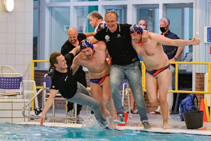 Coach Ingmar Veenhuis (links) en zijn assistent John van den Burg (tweede van rechts) halen een nat pak na het eindsignaal.