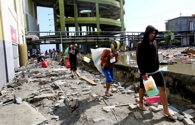 Inwoners van Palu met geplunderde goederen. Beeld AP