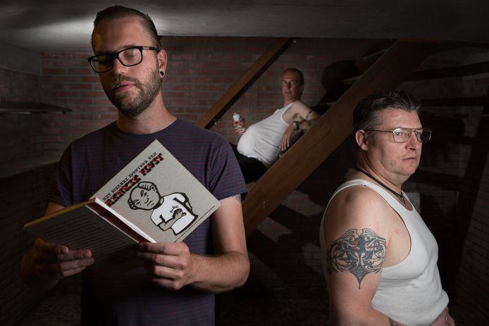 Bram de Krosse met het boekje over Henkie Fluit. De hoofdpersoon wordt op de achtergrond verbeeld door Peter van Hemert, bevriend met cartoonist Pieter Zandvliet (rechts).