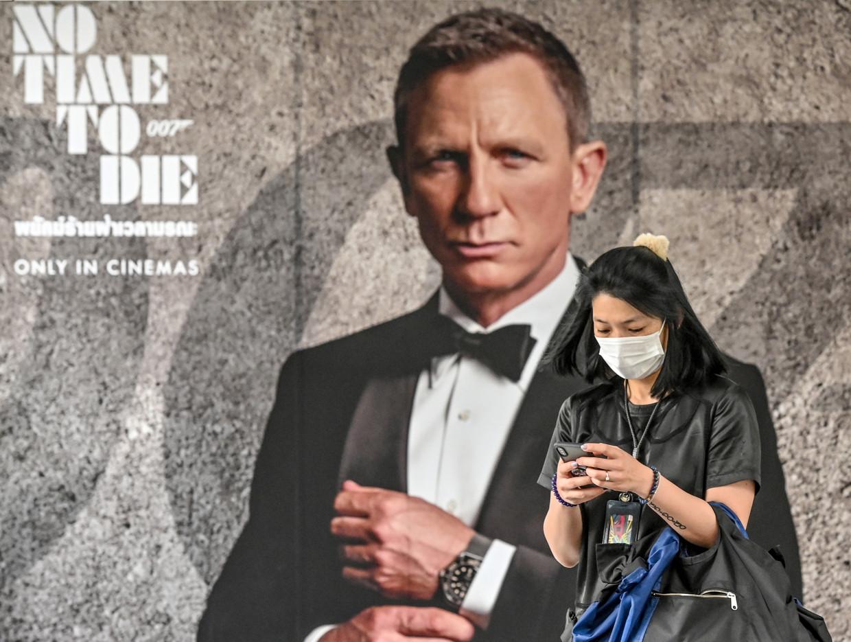 Een vrouw met een gezichtsmasker in Bangkok, voor een James Bond-poster. Beeld AFP