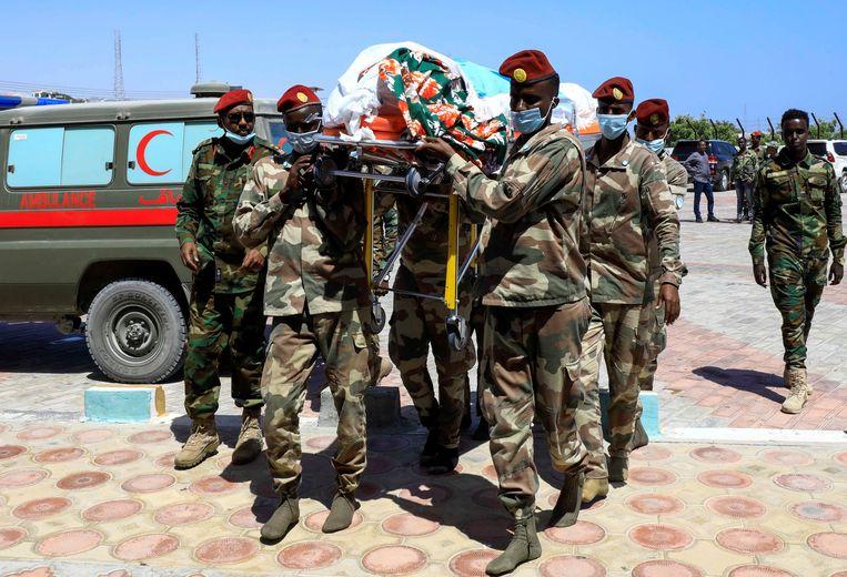 Soldaten dragen het lichaam van generaal Mohamed Noor Galal die omkwam tijdens de aanval op het Afrik Hotel.  Beeld REUTERS