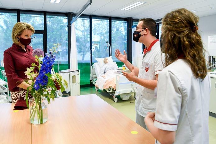 Koningin Mathilde, in gesprek met student Sybren Vanneste. We zien ook studente Marilies De Kegel.