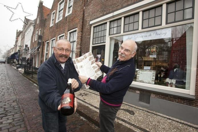 'Beheerders' Jan van den Berg (links) en Henk Graas verkopen in het nieuwe informatiepunt van stichting Kerst in de Vesting een eigen 'Kerst in de Vesting-glühwein' en de plattegrond van het evenement. foto Henri van der Beek