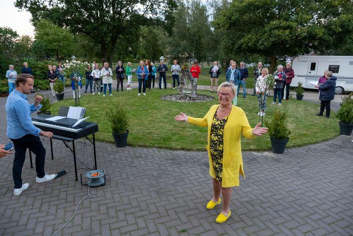 De Wapenveldse dirigent Jenny van Ark reageert verrast op de serenade van haar gemengd koor Arioso uit Heerde.