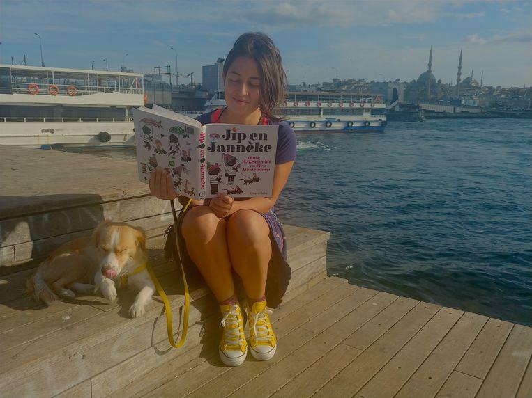 Taaldocent Ayca Aldatmaz bezig met haar Nederlandse lesstof bij de Galatabrug in Istanbul. Beeld Rob Vreeken