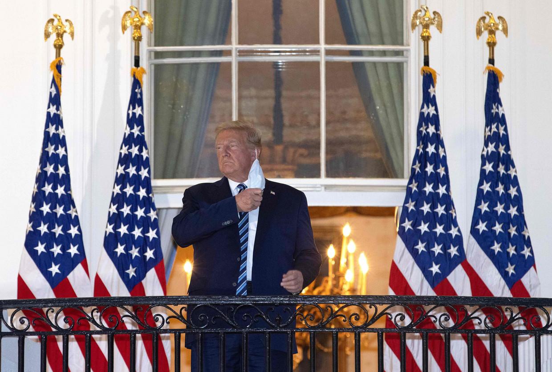 De Amerikaanse president Donald Trump verwijdert zijn mondkapje op het balkon van het Witte Huis. Beeld AFP
