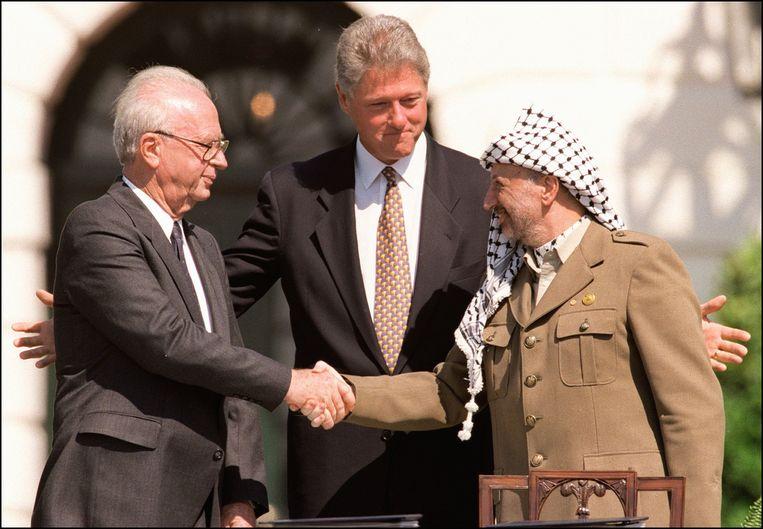 President Bill Clinton staat tussen de Palestijnse leider Yasser Arafat  en de Israelische premier Yitzahk Rabin voor het Witte Huis in 1993.  Beeld AFP/Getty Images