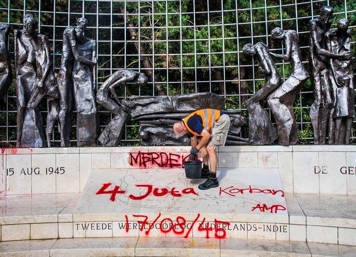 De rode en witte verf waarmee het Indisch monument is besmeurd wordt weggehaald.