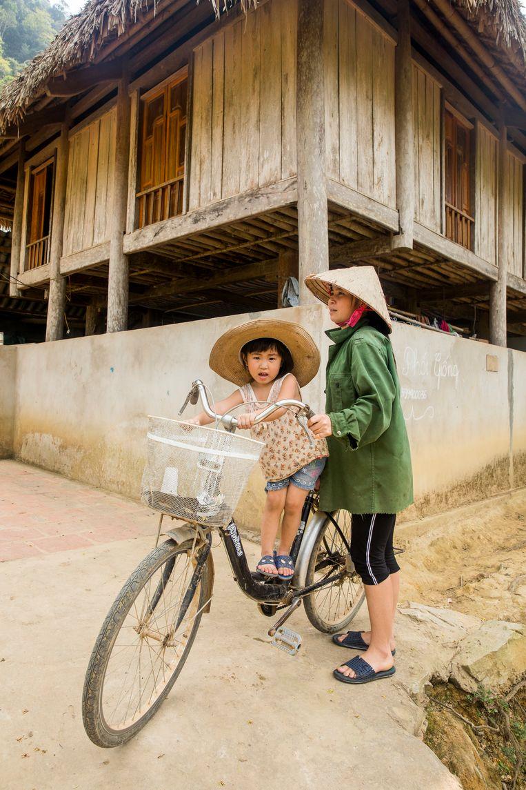 Kind en vrouw op de fiets voor een traditioneel palen huis in het Pu Loung gebied. Beeld Marie Wanders