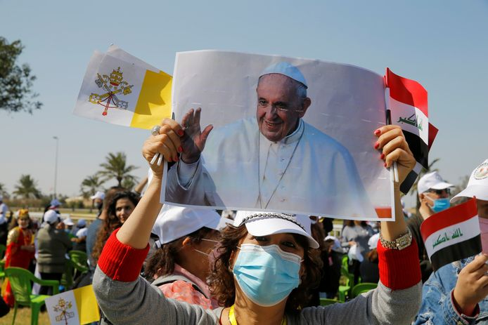 Une femme tient un portrait du pape François avant son arrivée à l'aéroport de Bagdad, le 5 mars 2021.