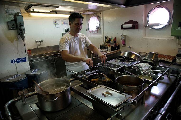 De chef-kok van de Aquarius aan het werk in zijn kombuis. De vluchtelingen krijgen bakjes tabouleh. Beeld Bram Janssen/AP