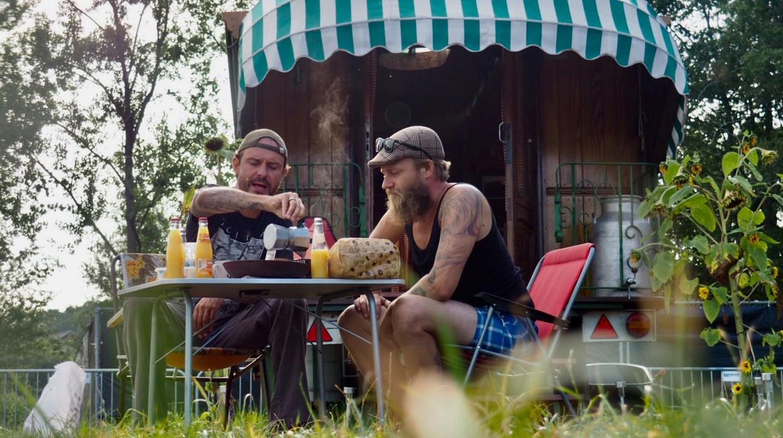 Tijs Vanneste (links) drinkt in 'De Kemping' een 'geui zjat kaffe'. Beeld VRT