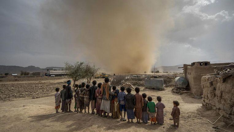 Kinderen kijken naar een kleine tornado in de woestijn in Jemen, 80 kilometer ten noorden van de hoofdstad Sanaa Beeld Giles Clarke / Getty