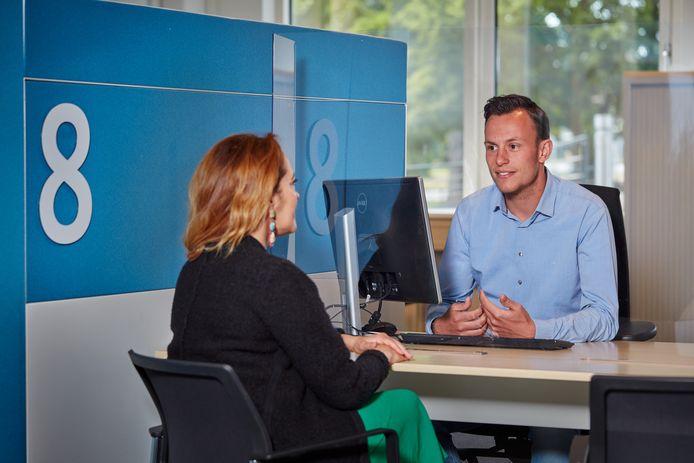Medewerkers en klanten worden gescheiden door dun plexiglas.