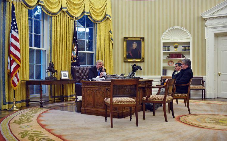 President Donald Trump in zijn Oval Office, vergezeld van Steve Bannon en de voormalige veiligheidsadviseur Michael Flynn. Beeld AFP