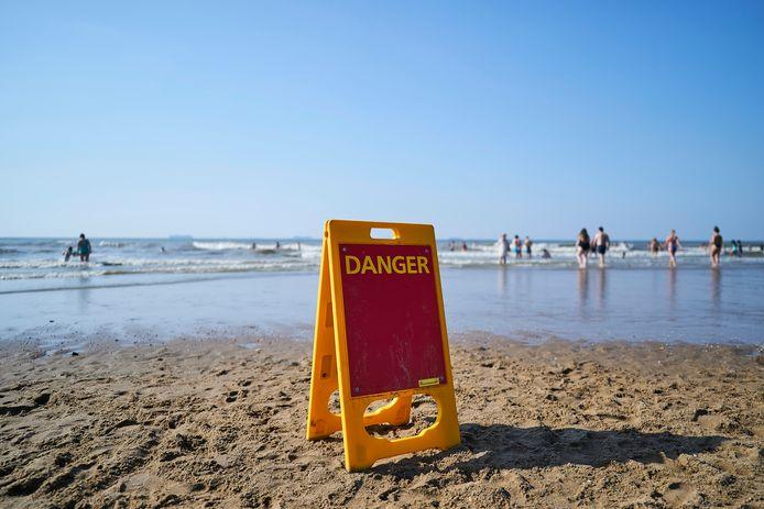 Een waarschuwingsbord op het Scheveningse strand, vanwege harde wind en gevaarlijke stroming.
