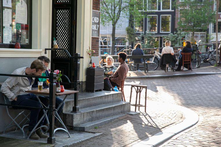 Nu het weer mag, gaan Amsterdammers het terras op. Of het nu in de schaduw is of midden op de stoep.  Beeld Amaury Miller