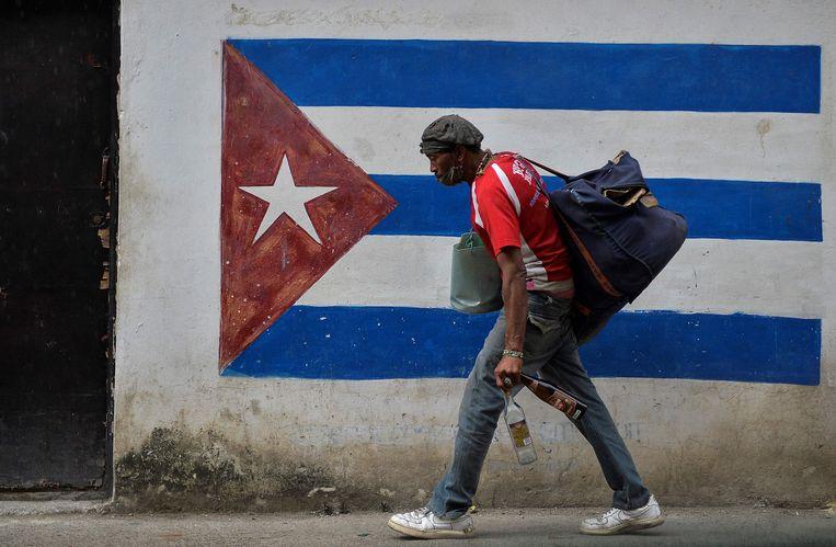Een man loopt langs een schildering van de Cubaanse vlag in Havana.  Beeld AFP