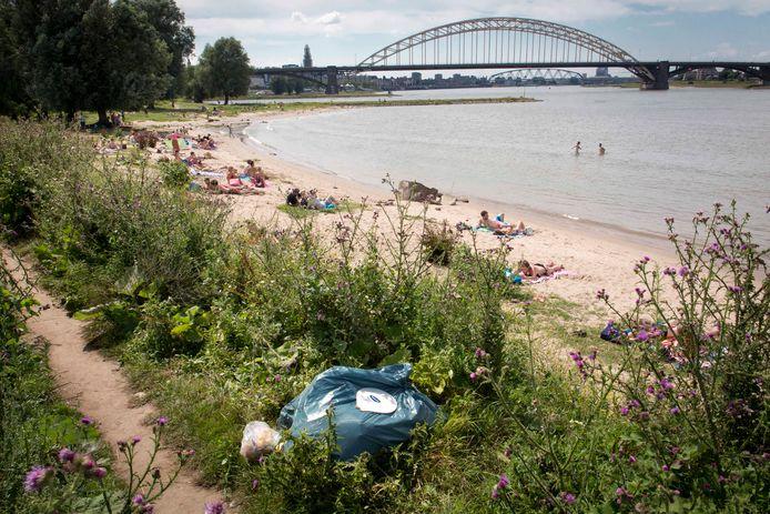 Zonaanbidders op een van de vele strandjes die de uiterwaarden van de Waal telt. Overal ligt rommel, zelfs complete vuilniszakken.
