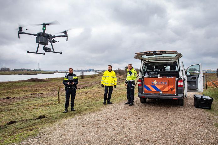 Dronepiloot Sander stuurt de drone omhoog. Politiemannen Dico de Ruiter en Teun Bussink (rechts) van het landelijke milieuteam kijken toe. Achterin de politiebus staat de laptop opengeklapt.