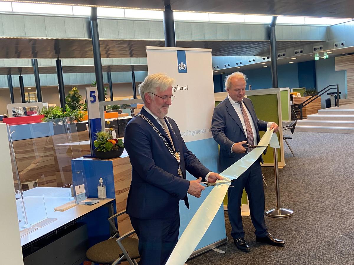 Burgemeester Erik van Merrienboer knipt samen met hoogste Belastingdienst-baas Peter Smink het lint door bij de balie in het stadhuis.