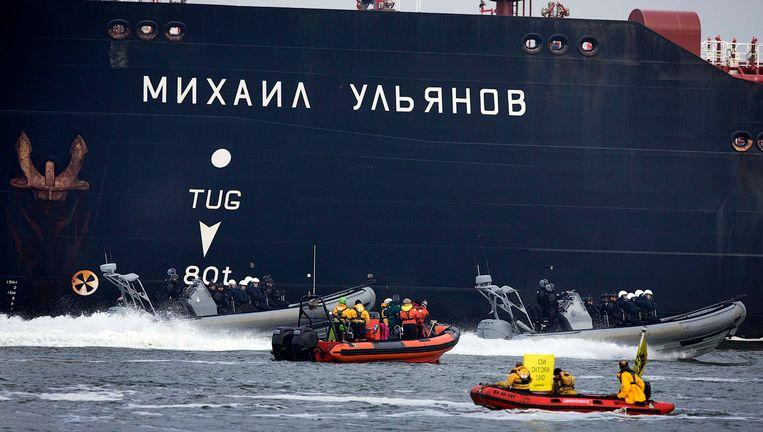 Politieboten varen tussen Greenpeace en de Russische olietanker Beeld REUTERS