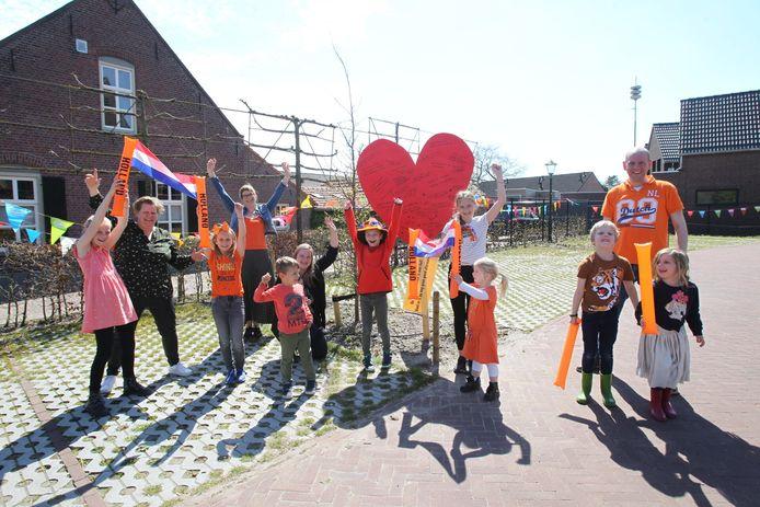 Inwoners en hun kinderen uit Oostelbeers die met een zelfgemaakte vlaggenslinger een stil protest voeren tegen de voorgenomen sluiting van hun basisschool De Beerze.