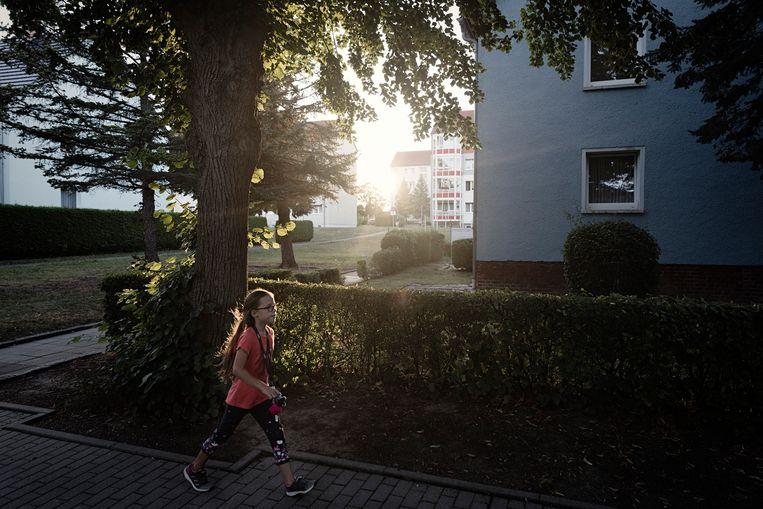 Een meisje wandelt voorbij het gebouw dat gebruikt werd voor vluchtelingenopvang.Dat werd in 2015 in brand gestoken.  Beeld Daniel Rosenthal