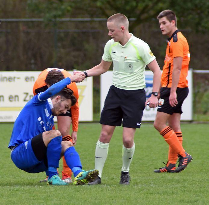 Scheidsrechter Niels Boel helpt een speler van FC Axel overeind.