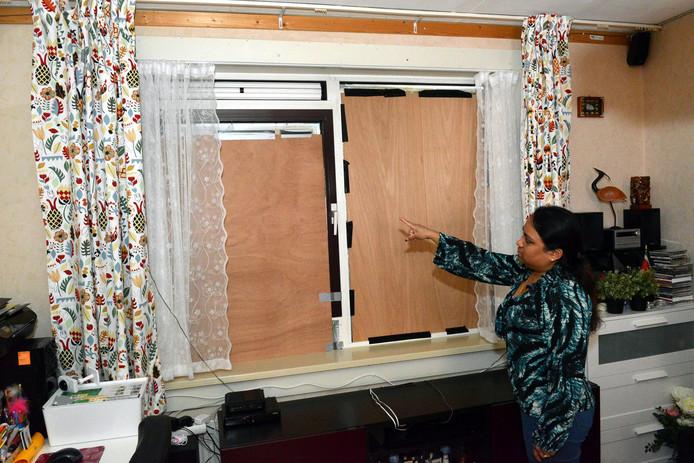 Marina wijst naar de ingehakte ramen.