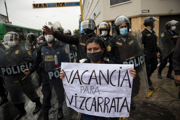 Demonstrant houdt een bord op met 'vacature voor vizacarrata', en maakt gebruik van de spelling van de achternaam van president Vizcarra om hem een rat te noemen. Beeld AP