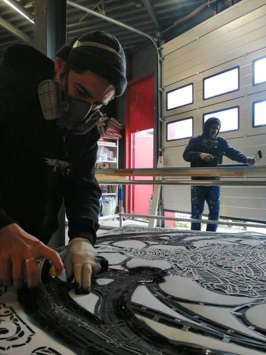 MonkeyBird Crew, het Franse kunstenaarsduo Louis Boidron en Edouard Egéa uit Bordeaux, aan het werk in Breda. Met de hand knippen ze minutieus patronen om later te schilderen
