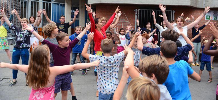 Enkele enthousiaste juffen doen de aanstekelijke danspasjes voor op de speelplaats.