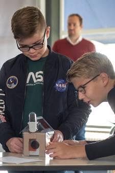 Reave en Levi leren met een kartonnetje in de spouwmuur hoe goed isolatie werkt