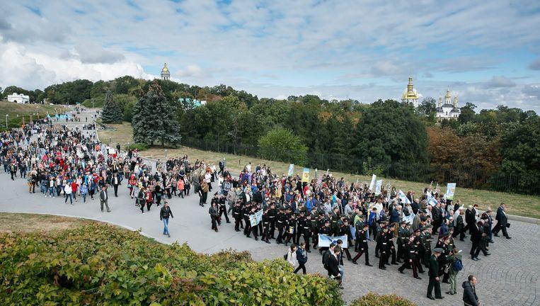 Oekraiense burgers dragen bloemen en slpandoeken tijdens een mars op de Internationale Dag voor de Vrede op 21 september. Beeld EPA
