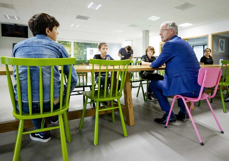 Slob praat met leerlingen op middelbare school Lumion in Amsterdam. Hun eerste schooldag zag er vanwege het coronavirus anders uit. Zo moeten leerlingen vaak hun handen wassen en worden lokalen regelmatig gelucht.  Beeld ANP/Robin van Lonkhuijsen
