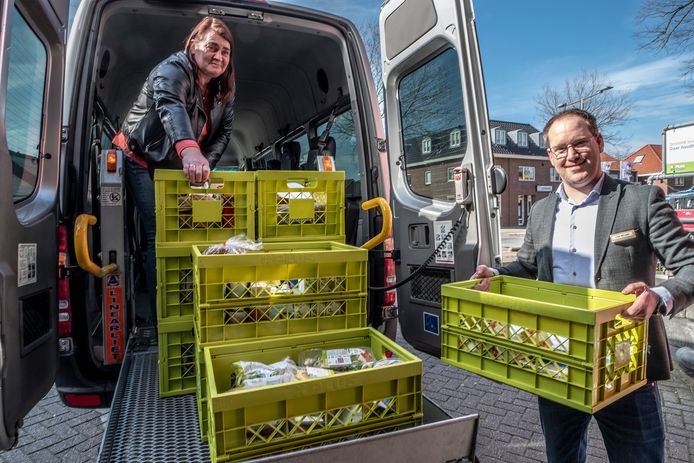 Cor Willem Visser (rechts) van de PLUS en Monique van Kuil van taxi Van der Wielen met de boodschappen die rondgebracht worden.