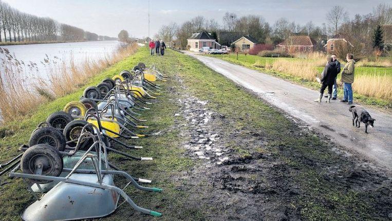 Inwoners van Woltersum bij een van de zwakkere plekken in de dijk langs het Eemskanaal. ©REYER BOXEM Beeld