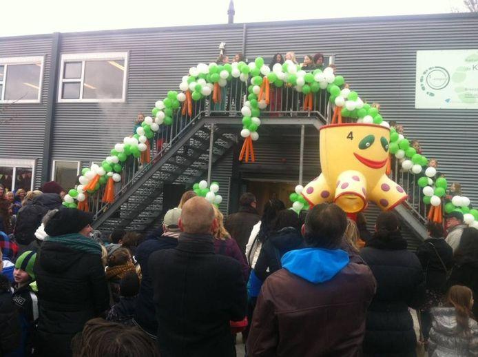 Kinderen zingen het Kringlooplied op de brandtrap van het gebouw.