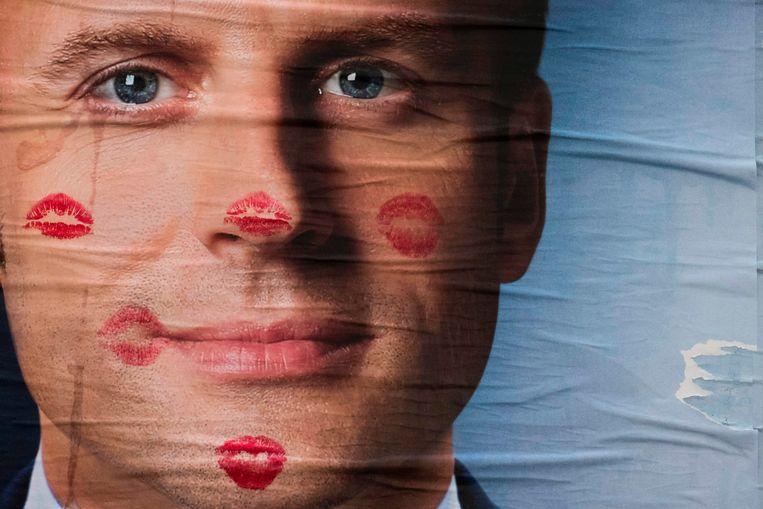 Een bekladde campagneposter van Emmanuel Macron. Beeld AFP
