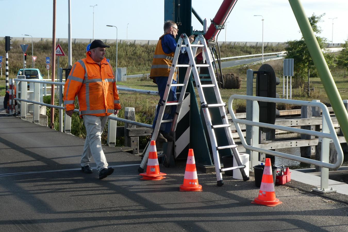 Wesley Libregts (l) ziet toe op de veiligheid op de Dungense Brug tijdens onderhoudswerk eerder dit jaar.