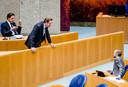 Demissionair minister Hugo de Jonge van Volksgezondheid, Welzijn en Sport (CDA, midden, staand) in gesprek met SP-kamerlid Maarten Hijink (rechts, zittend) in de Tweede Kamer.