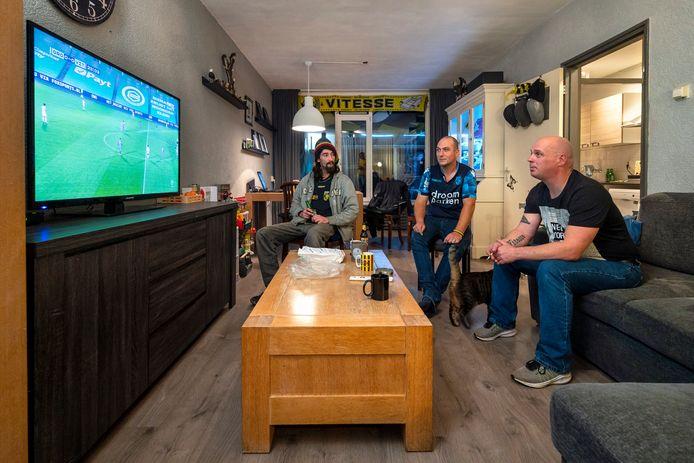 Yilmaz Wagendorp (l) kijkt met voetbalvrienden Menno (m) en Remco Inkenhaag bij gebrek aan stadionbezoek op de televisie naar de voetbalwedstrijden van Vitesse.